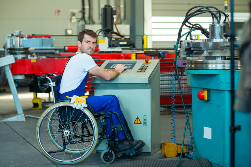 Disabled worker in a wheelchair on a factory machine.