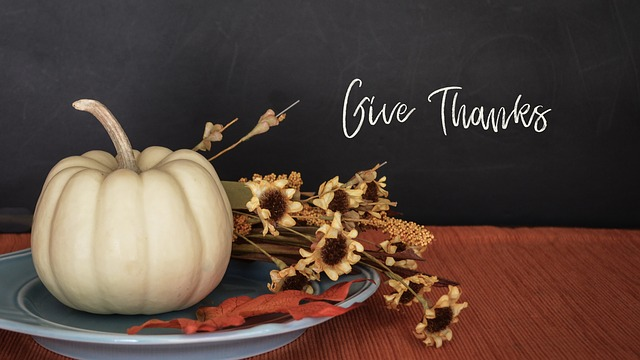 The words Give Thanks with a white pumpkin and fall flower display